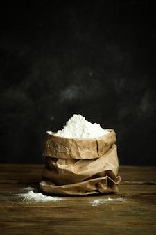 Farinha para assar massa de pizza, pão e macarrão em uma mesa de madeira e fundo escuro. conceito de cozinhar em casa
