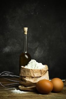 Farinha para assar massa de pizza, pão e macarrão em uma mesa de madeira e fundo escuro.