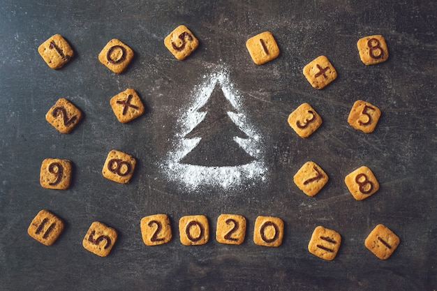 Farinha silhueta árvore de natal com dígitos de cookies