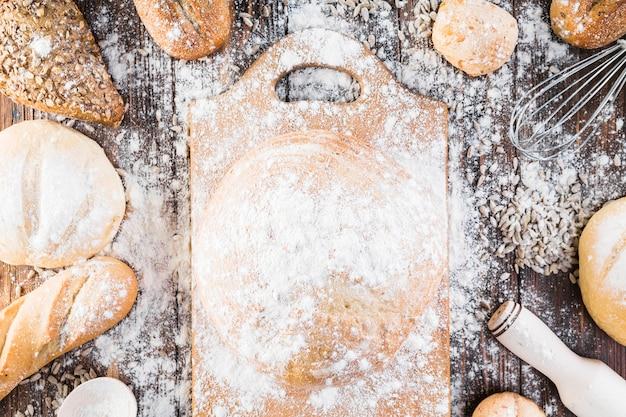 Farinha sobre a tábua de cortar e variedade de pães na mesa