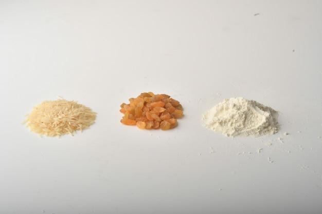 Farinha, trigo, arroz, passas e moedas em um fundo branco