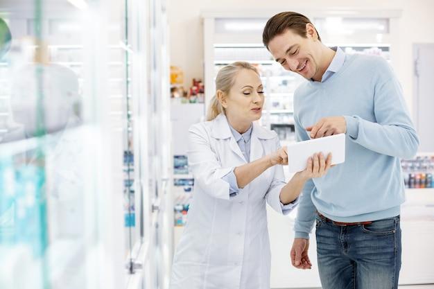 Farmacêutica ajudando um homem bonito
