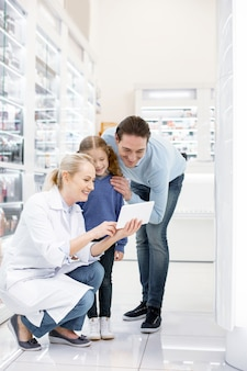 Farmacêutica ajudando uma família em uma drogaria