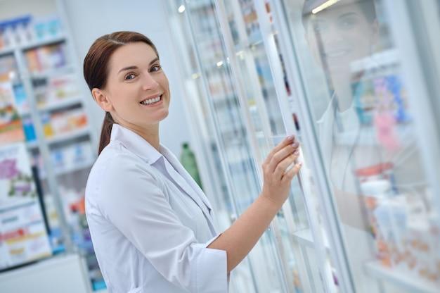 Farmacêutica alegre abrindo prateleira com remédios