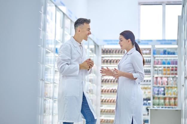 Farmacêutica atraente de cabelos escuros conversando com seu colega de cabelos grisalhos feliz no armazém da farmácia