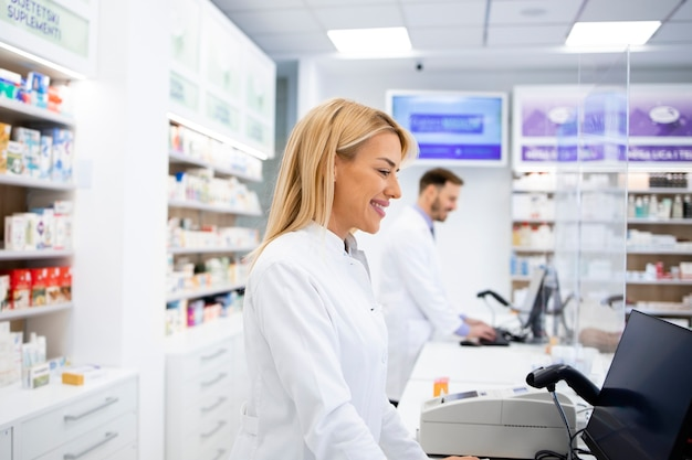 Farmacêutica caucasiana feminina que vende medicamentos na farmácia.