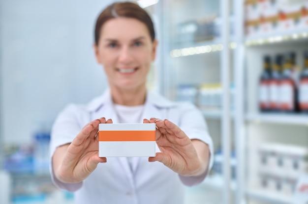 Farmacêutica com as mãos de uma mulher mostrando a caixa de remédios