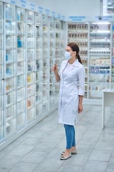 Farmacêutica examinando remédios nas prateleiras