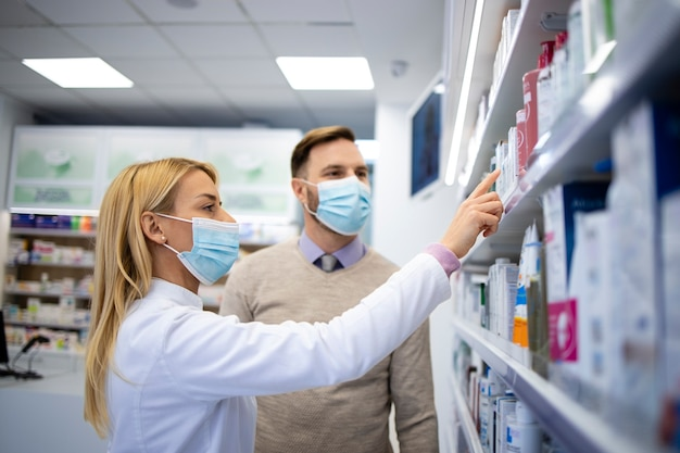 Farmacêutica feminina que vende novos produtos ao cliente na loja da farmácia.