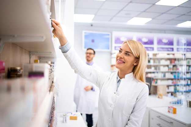 Farmacêutica feminina trabalhando na loja da farmácia, tomando remédios da prateleira.