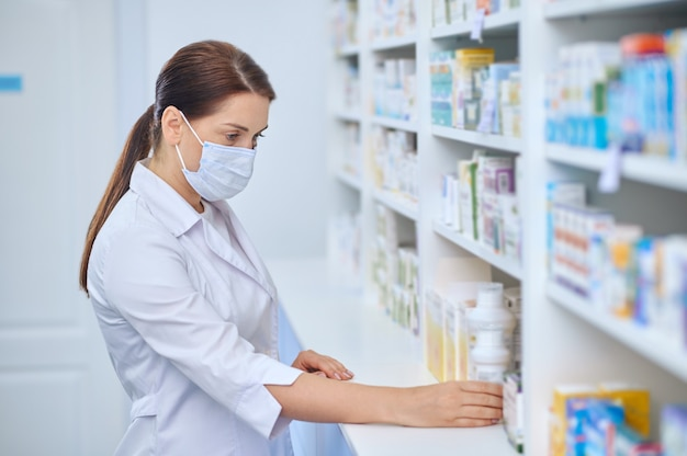 Farmacêutica interessada examinando remédios nas prateleiras
