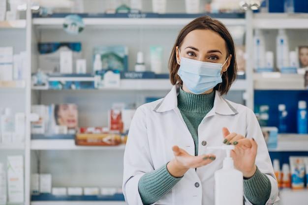 Farmacêutica jovem desinfetando mãos com sanitazer