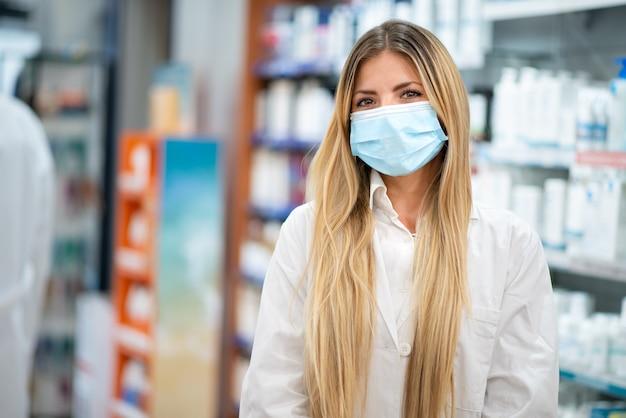 Farmacêutica jovem loira sorridente usando máscara de coronavírus cobiçado dentro de sua farmácia