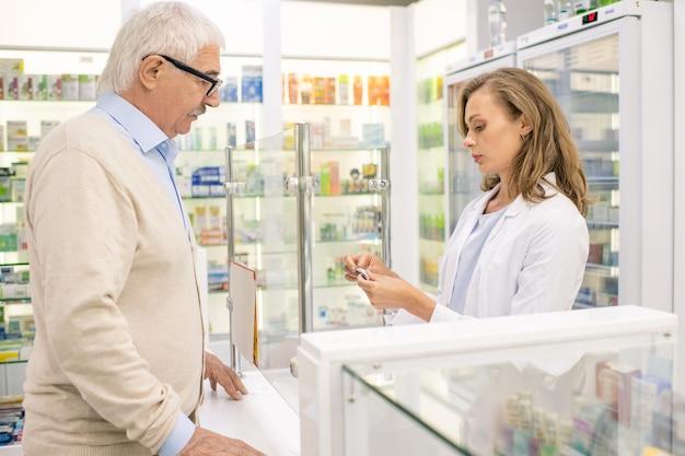 Farmacêutica muito jovem ou assistente de drogaria, consultando um cliente sênior do sexo masculino e recomendando-o para comprar um novo medicamento eficaz