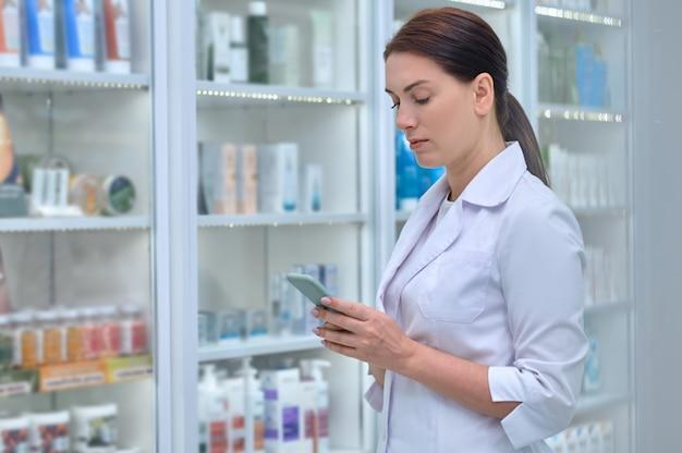 Farmacêutica séria com uma túnica branca, focada na leitura de uma mensagem de texto em seu smartphone