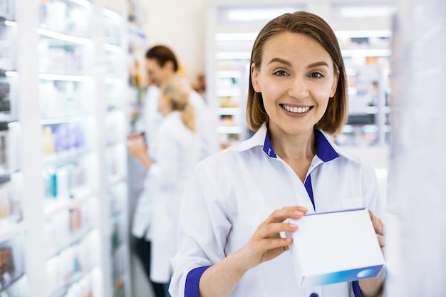 Farmacêutica séria segurando um medicamento nas mãos, observando atentamente a composição do medicamento