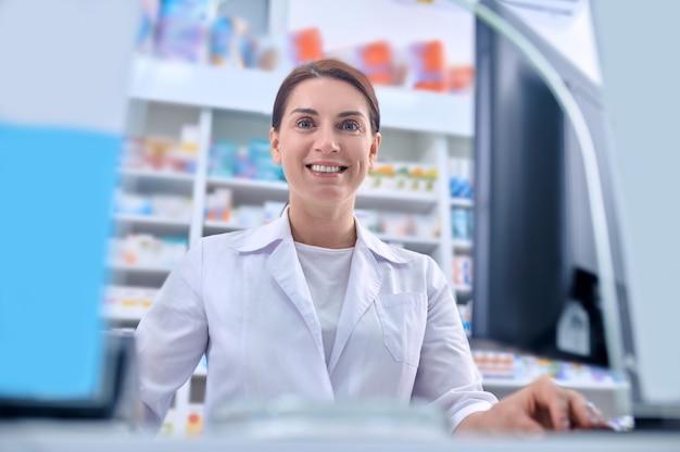 Farmacêutica simpática e sorridente à espera de novos clientes