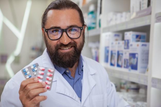 Farmacêutico alegre vendendo medicação em sua farmácia
