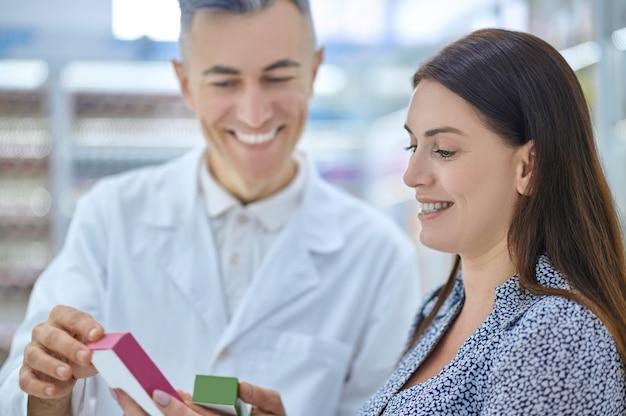 Farmacêutico amigável que recomenda novos medicamentos a um cliente