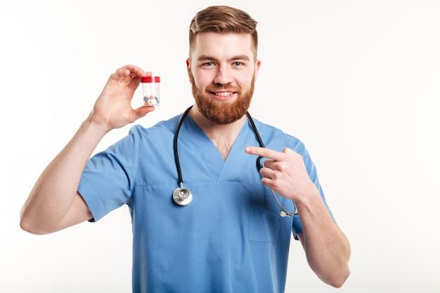 Farmacêutico amigável sorridente, apontando o dedo na garrafa com comprimidos