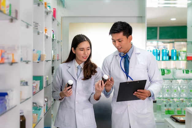 Farmacêutico asiático da jovem mulher e do homem com um sorriso amigável encantador e verificação do inventário na farmácia da farmácia.