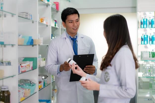 Farmacêutico asiático da jovem mulher e do homem que verifica o inventário na farmácia da farmácia.