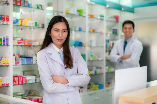 Farmacêutico asiático de duas jovens mulheres e homens com um sorriso amigável encantador que está com os braços cruzados na farmácia da farmácia. medicina, farmácia, cuidados de saúde e conceito de pessoas.