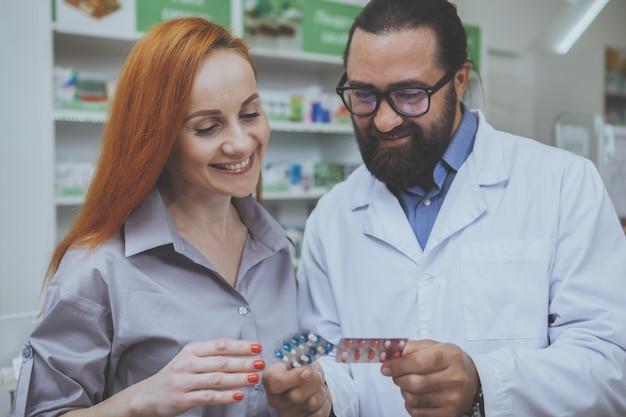 Farmacêutico barbudo vendendo comprimidos para um cliente do sexo feminino