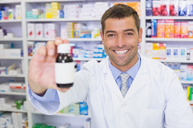 Farmacêutico bonito mostrando o frasco de medicamento