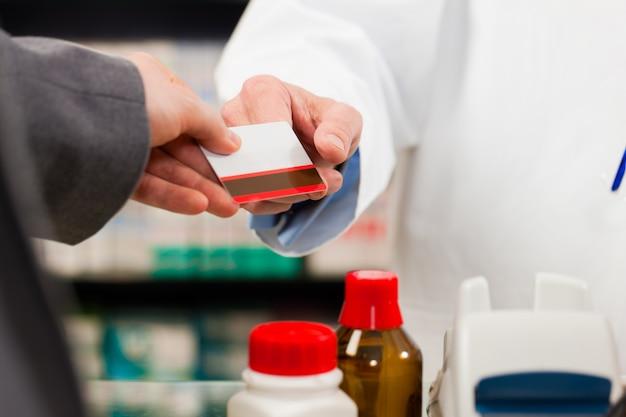 Farmacêutico com cliente pagador em farmácia