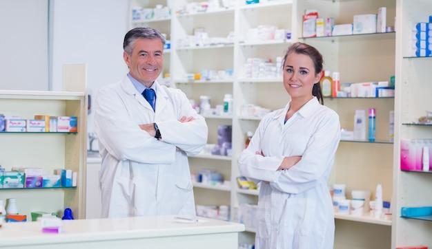 Farmacêutico com seu estagiário em pé com os braços cruzados