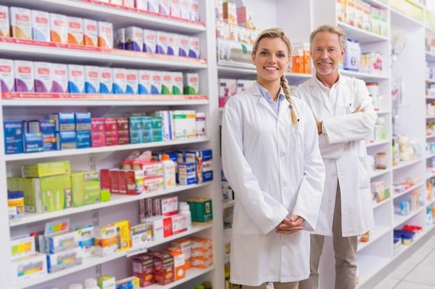Farmacêutico com seu estagiário permanente e sorrindo para a câmera