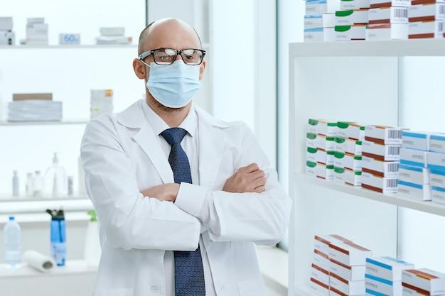 Farmacêutico com uma máscara protetora de pé em sua farmácia. foto com uma cópia-espaço.
