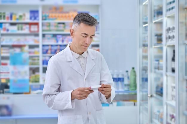 Farmacêutico concentrado olhando para um medicamento em suas mãos