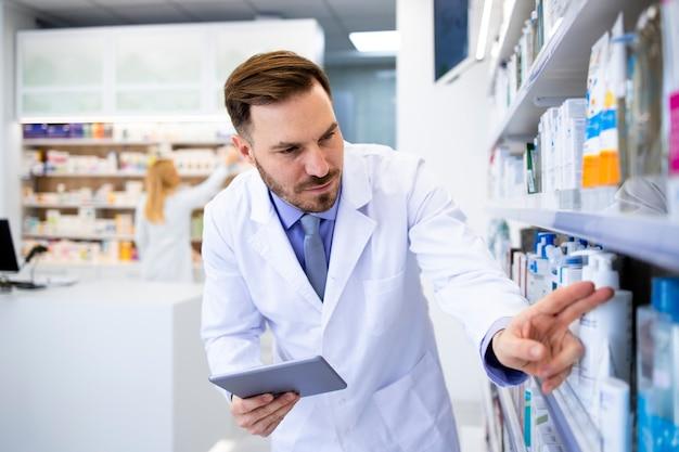 Farmacêutico contando medicamentos e verificando o fornecimento no computador tablet na loja da farmácia.