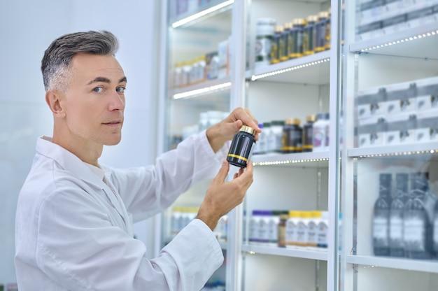 Farmacêutico de meia-idade calmo com um frasco de remédio de plástico lacrado em frente à vitrine da farmácia