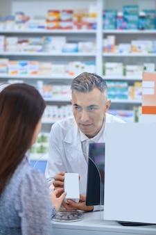 Farmacêutico de meia-idade e cabelos grisalhos atendendo uma cliente