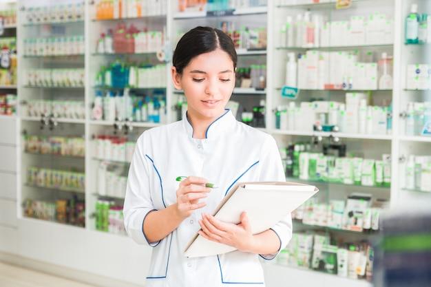 Farmacêutico de mulher inteligente e confiante, segurando uma pasta e fazer anotações