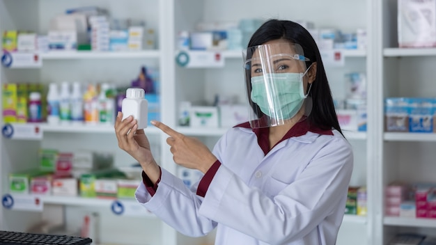 Farmacêutico de mulheres asiáticas profissionais com máscara protetora no rosto, trabalhando em uma drogaria moderna e mostrando o frasco de remédio branco em uma loja da farmácia tailândia