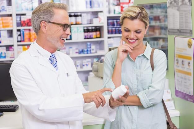 Farmacêutico e cliente olhando medicamentos