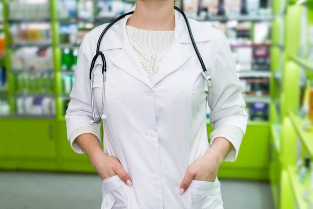 Farmacêutico em pé na drogaria, mãos no bolso do robe
