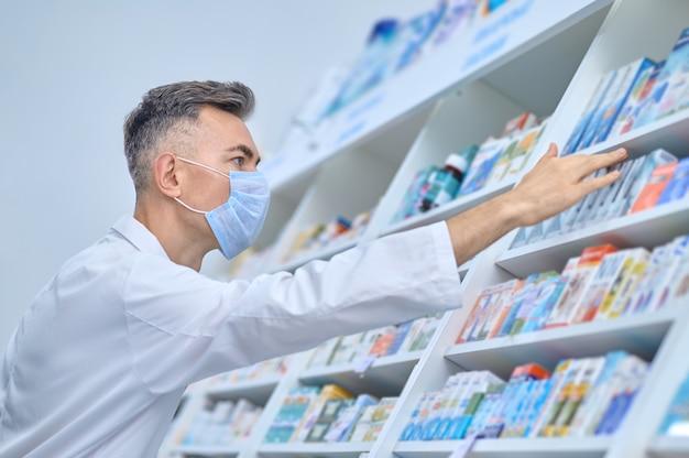 Farmacêutico escolhendo um medicamento para um cliente