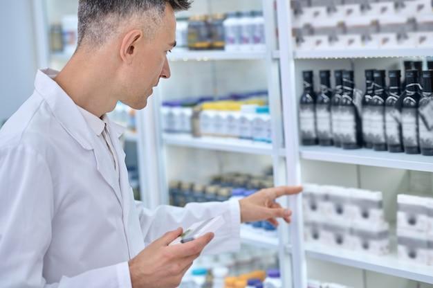 Farmacêutico experiente em uma túnica branca focado na busca pelo remédio certo na vitrine da farmácia