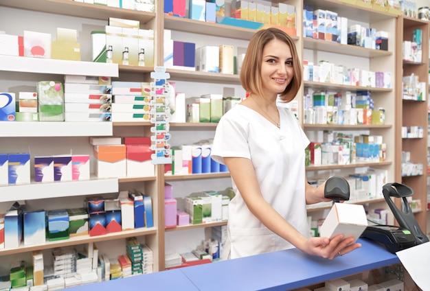 Farmacêutico feliz que digitaliza o código de barras do medicamento.