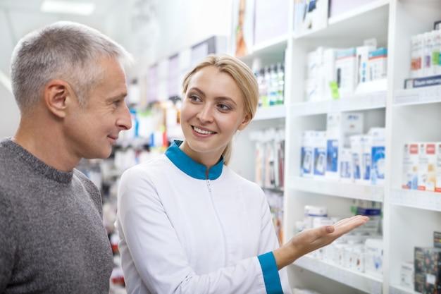 Farmacêutico fêmea adorável que ajuda seu cliente