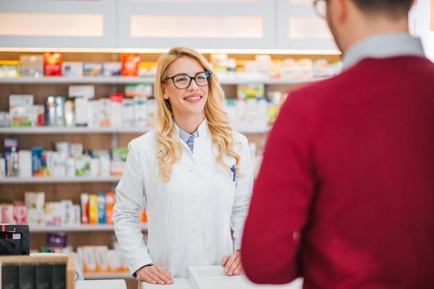 Farmacêutico fêmea bonito que fala com um cliente masculino.