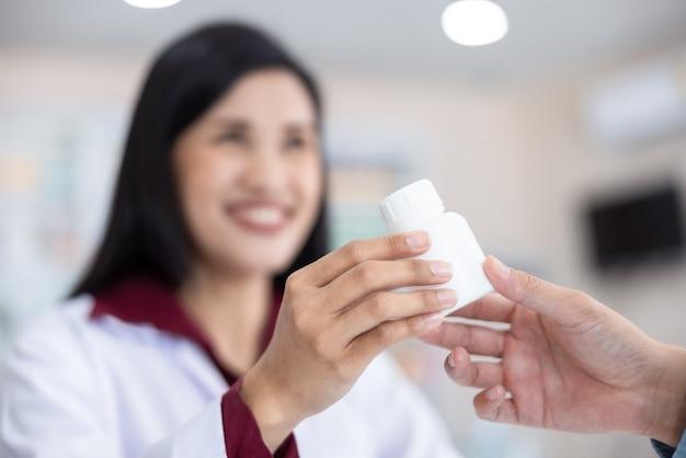 Farmacêutico feminino asiático segurando um frasco de remédio branco dando conselhos ao cliente na farmácia ou na farmácia tailândia close-up e foco seletivo