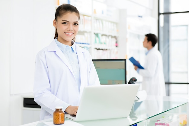 Farmacêutico feminino asiático sorridente, trabalhando na farmácia