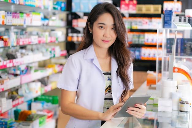 Farmacêutico feminino asiático usa tablet digital na farmácia