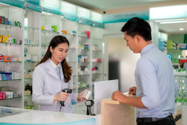 Farmacêutico feminino jovem asiático com um sorriso amigável adorável digitalizar código de barras na caixa do medicamento